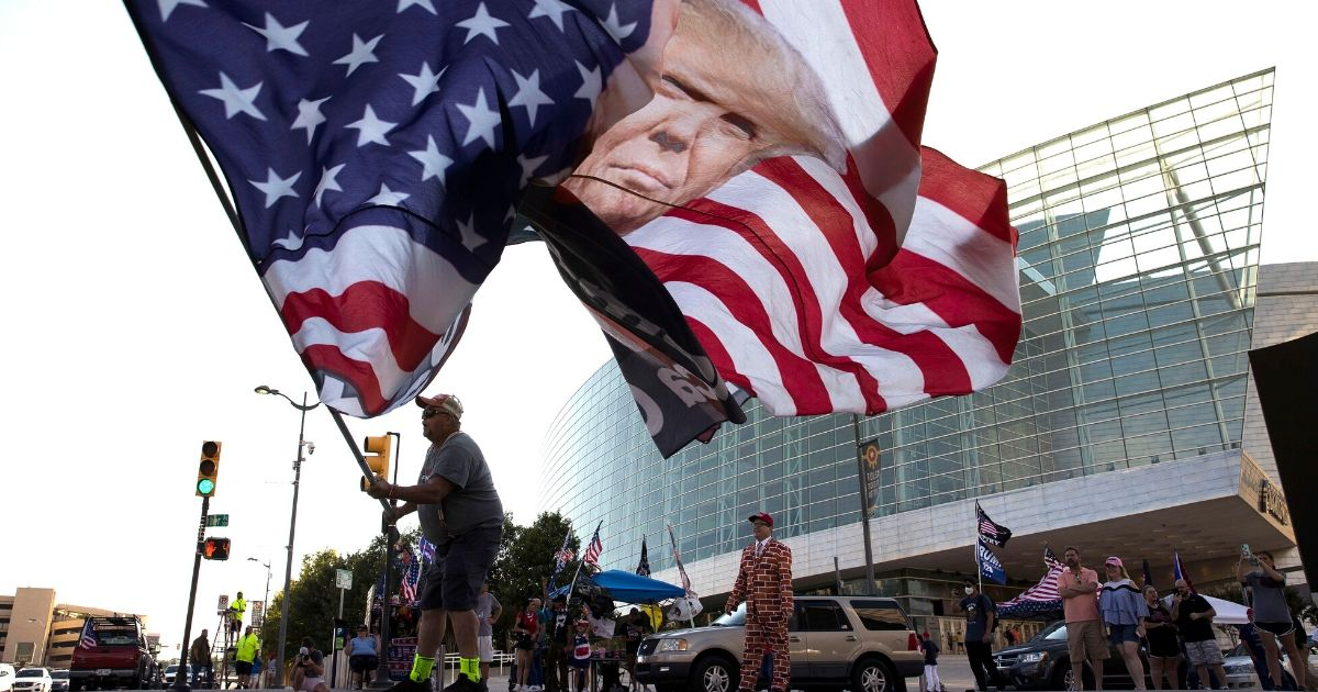 Trump supporter Randall Thom waves a giant Trump flag outside the BOK Center on June 18, 2020, in Tulsa, Oklahoma. Trump is scheduled to hold his first political rally since the start of the coronavirus pandemic at the BOK Center on Saturday.