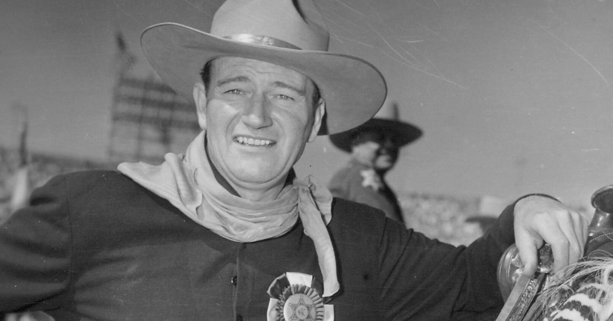 Actor John Wayne stands with a horse in 1954.