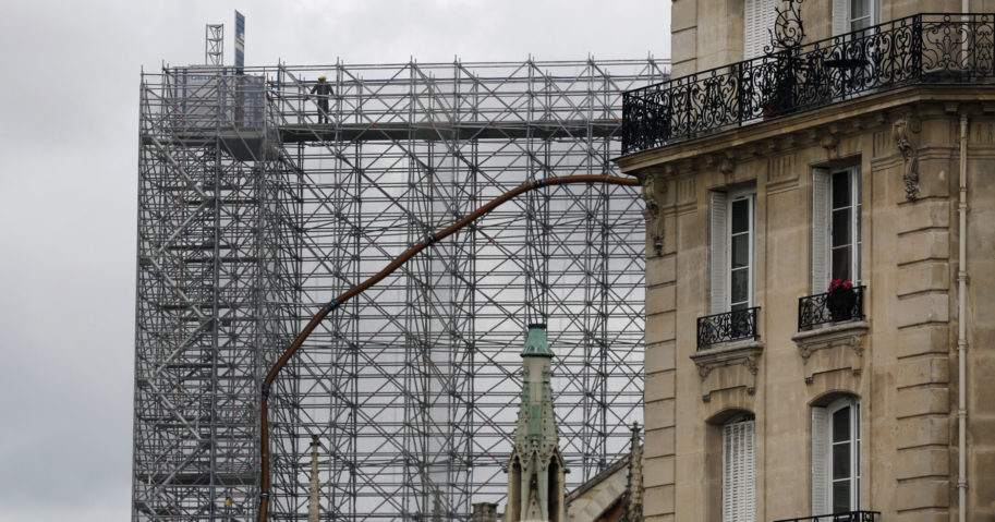 A worker stands on scaffolding at Notre Dame Cathedral on July 10, 2020, in Paris. Notre Dame will be rebuilt just the way it stood before last year's devastating fire.