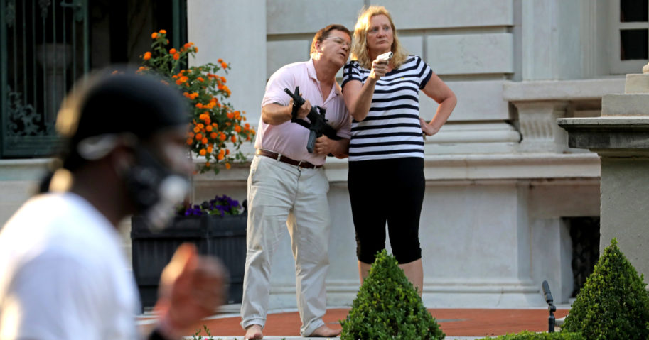 """In this June 28, 2020, file photo, armed homeowners Mark and Patricia McCloskey confront protesters outside their home in St. Louis. President Donald Trump believes St. Louis' top prosecutor committed an """"egregious abuse of power"""" in charging the couple, White House press secretary Kayleigh McEnany said on July 21."""