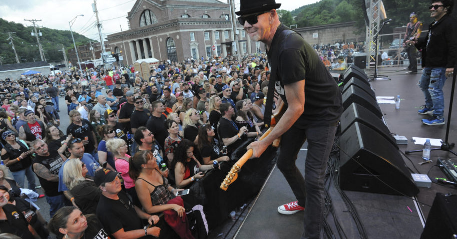 Mark Kendall, center, with the band Great White, performs in Johnstown, Pennsylvania, in June 2018. Great White, a metal band, has apologized for performing at an outdoor North Dakota concert where crowd members did not wear face masks amid the coronavirus pandemic.