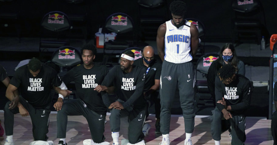 The Orlando Magic's Jonathan Isaac stands as others kneel during the national anthem before the start of an NBA basketball game between the Brooklyn Nets and the Orlando Magic on July 31, 2020, in Lake Buena Vista, Florida.