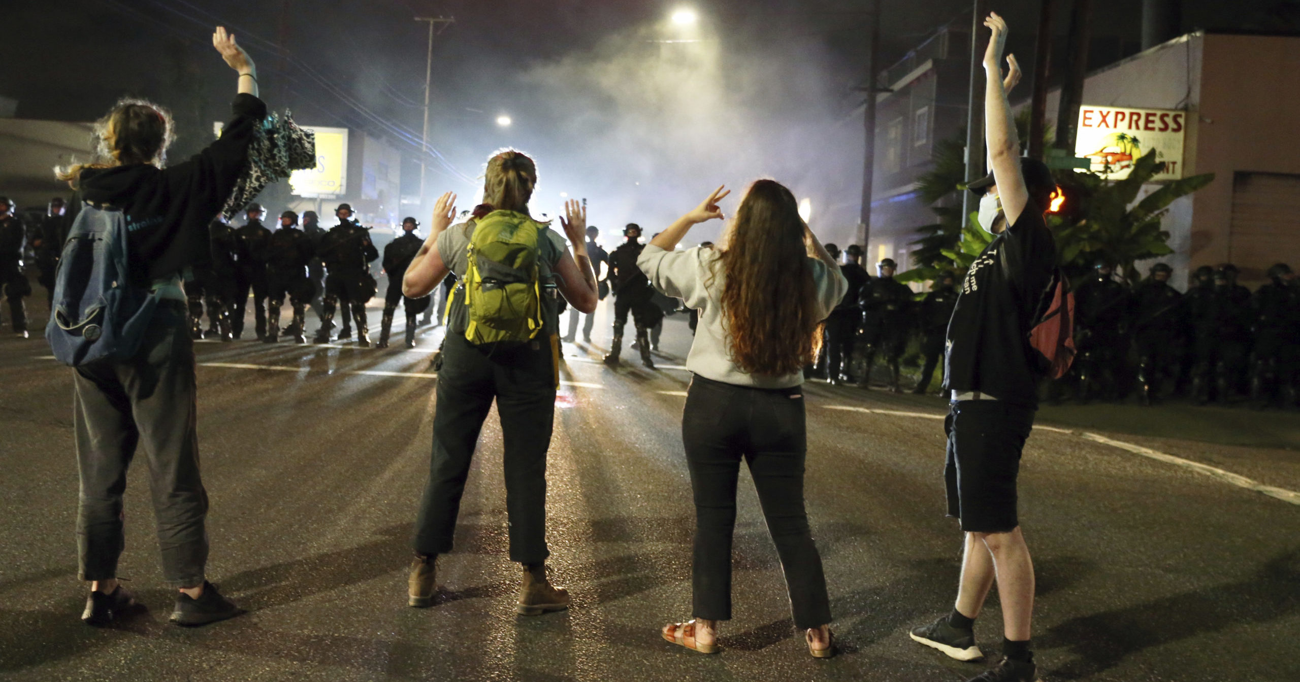 In this June 30, 2020, file photo, police stand in front of protesters gathered outside Portland Police Union headquarters in Portland, Oregon.