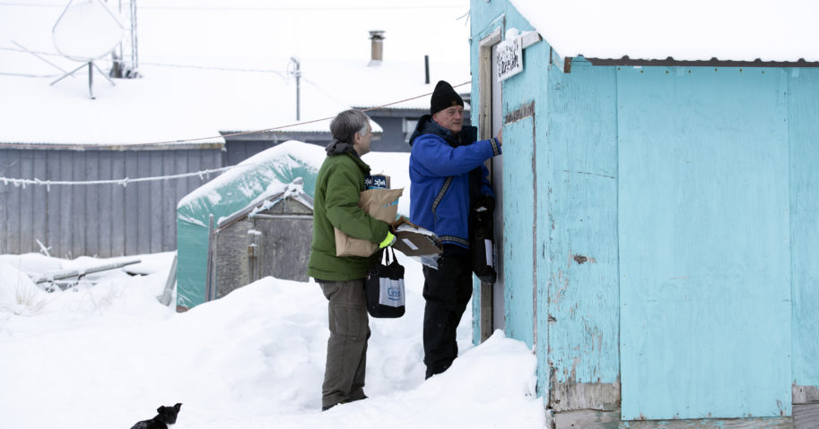 In this Jan. 21, 2020, file photo, Census Bureau director Steven Dillingham, right, knocks on the door alongside census worker Tim Metzger as they arrive to conduct the first enumeration of the 2020 Census in Toksook Bay, Alaska. Thousands of census takers are about to begin the most labor-intensive part of America's once-a-decade headcount. The 2020 census started in January in rural Alaska where census takers visited homes much earlier than the rest of the country because of the difficulty in reaching those places.