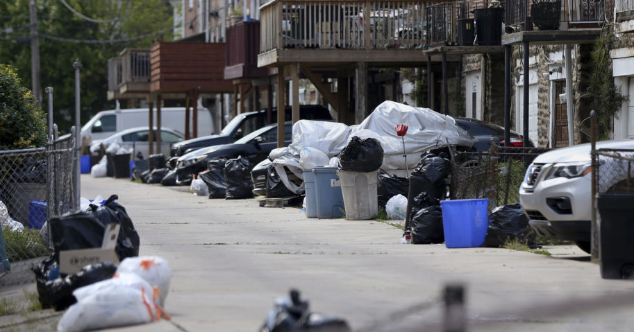 In this photo from May 13, 2020, bags of garbage sit along the street in Philadelphia's Ogontz section. Households are generating more trash as people stay home due to shutdown restrictions.
