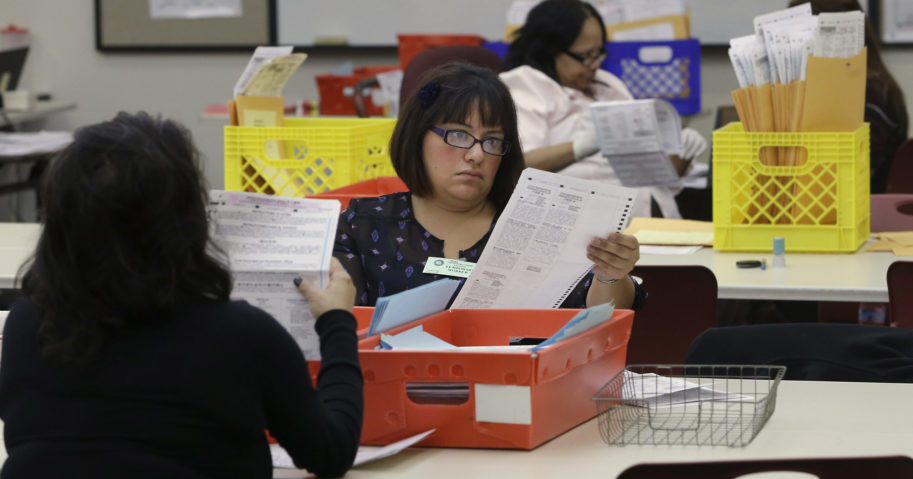Lydia Harris, a temporary worker, looks over a mail-in ballot before it is sent to be counted Nov. 12, 2014, in Sacramento, California.