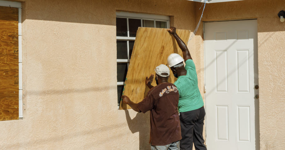 Residents cover a window with plywood in preparation for the arrival of Hurricane Isaias in Freeport, Grand Bahama, Bahamas, on July 31, 2020.