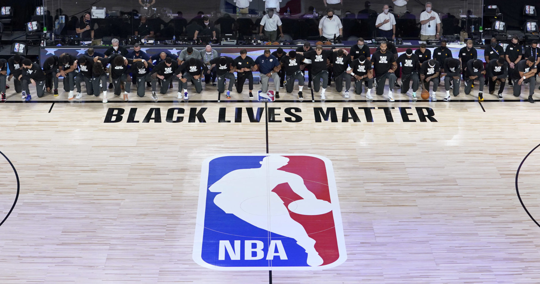 """Members of the New Orleans Pelicans and Utah Jazz kneel together in front of a """"Black Lives Matter"""" logo on the court during the national anthem before the start of a game July 30, 2020, in Lake Buena Vista, Florida."""