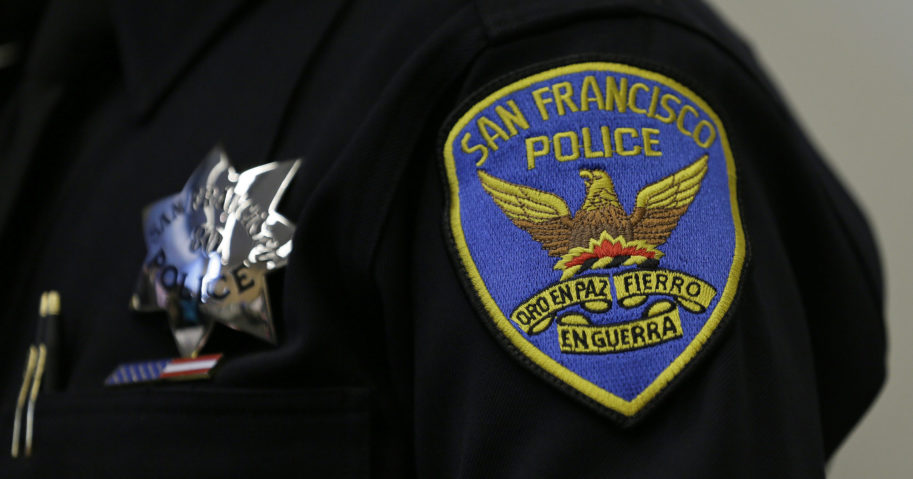 This April 29, 2016, file photo shows a patch and badge on the uniform of a San Francisco police officer. The San Francisco Police Department will stop releasing mug shots in an effort to stop perpetuating racial stereotypes, the police chief announced on July 1, 2020.