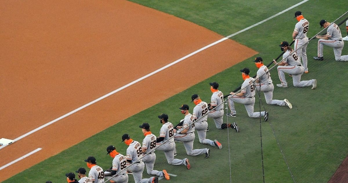 Sam Coonrod of the San Francisco Giants stands while his teammates kneel during a moment of silence prior to their Opening Day game against the Los Angeles Dodgers at Dodger Stadium on July 23, 2020.