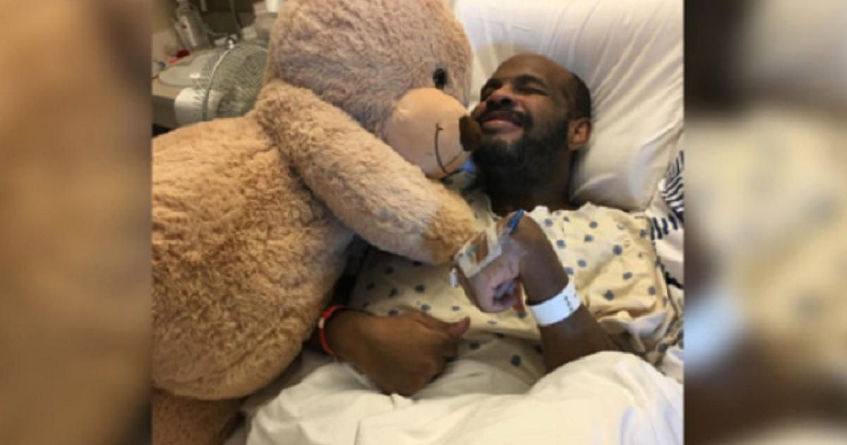A photo of Michael Hickson in a hosptial bed with a larged stuffed bear.