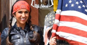 Lauren Boebert, a Republican congressional candidate in Colorado, holds an American flag.