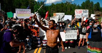 Activists and members of different tribes from the region block the road to Mount Rushmore National Monument as they protest in Keystone, South Dakota on July 3, 2020, during a demonstration around the Mount Rushmore National Monument and the visit of US President Donald Trump.