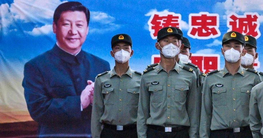 Soldiers of the People's Liberation Army's Honour Guard Battalion wear protective masks as they stand at attention in front of photo of Chinese President Xi Jinping at their barracks outside the Forbidden City near Tiananmen Square on May 20, 2020, in Beijing, China.