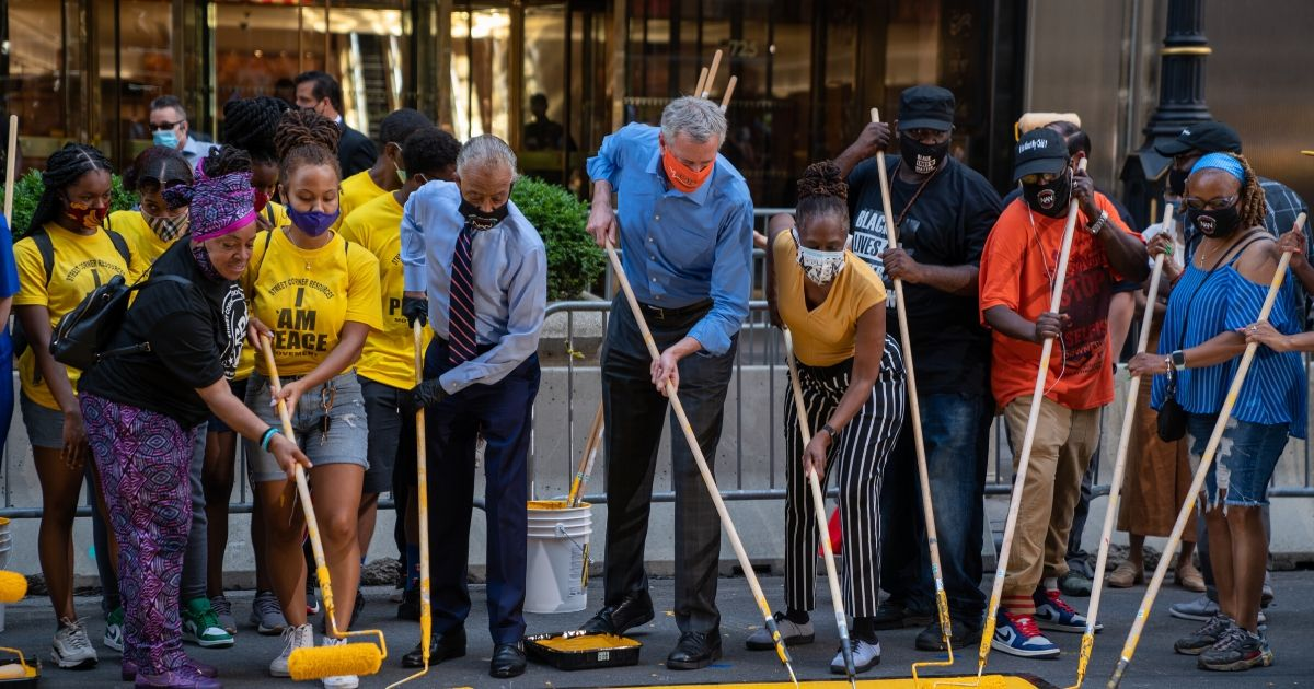 New York City Mayor Bill de Blasio (center), the Rev. Al Sharpton (wearing a tie) and others paint a Black Lives Matter mural on Fifth Avenue directly in front of Trump Tower on July 9, 2020.