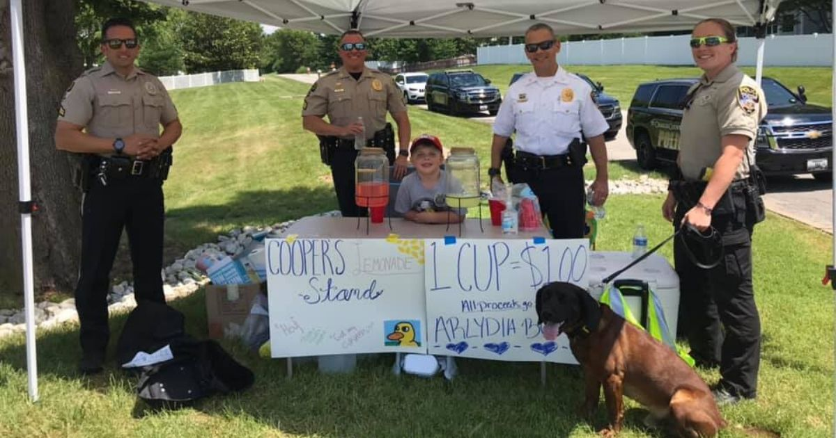 Police officers pose with 5-year-old Cooper Wallweber at a benefit lemonade stand he set up.