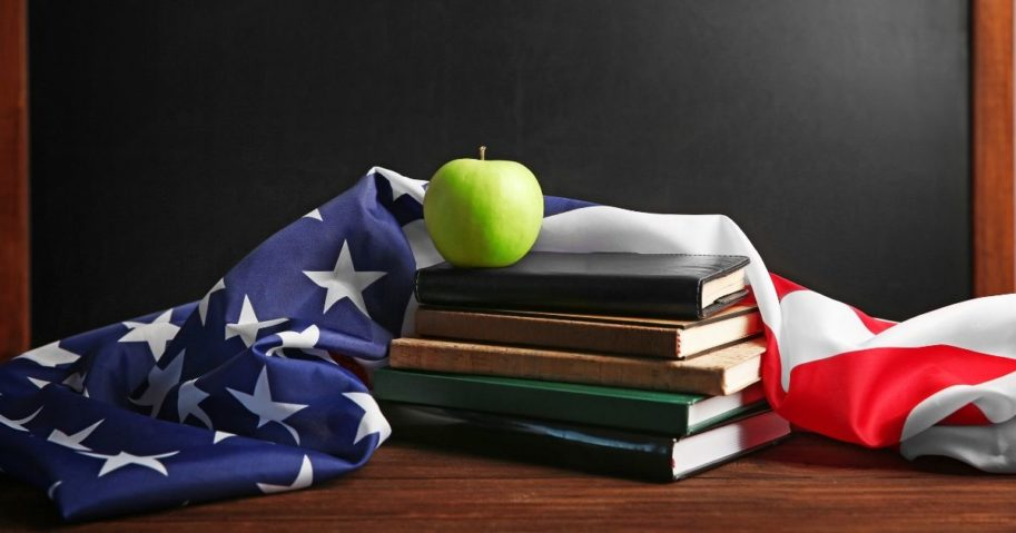 American flag with books and apple on chalk board background.