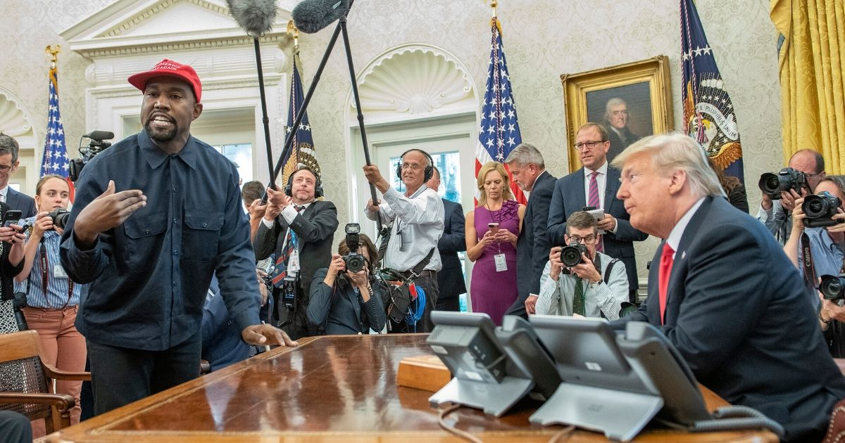 Photographers and cameramen surround rapper Kanye West and President Donald Trump during an October 2018 Oval Office meeting.