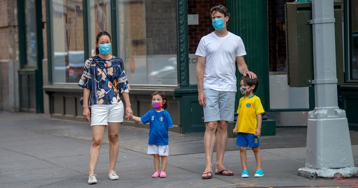 A family wearing masks waits to cross the street on June 24, 2020, in New York City.