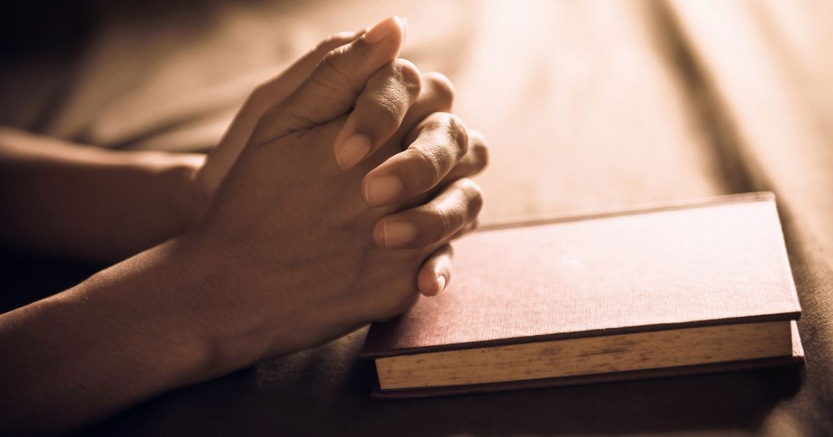 Stock image of a person praying with their hands folded over a Bible.