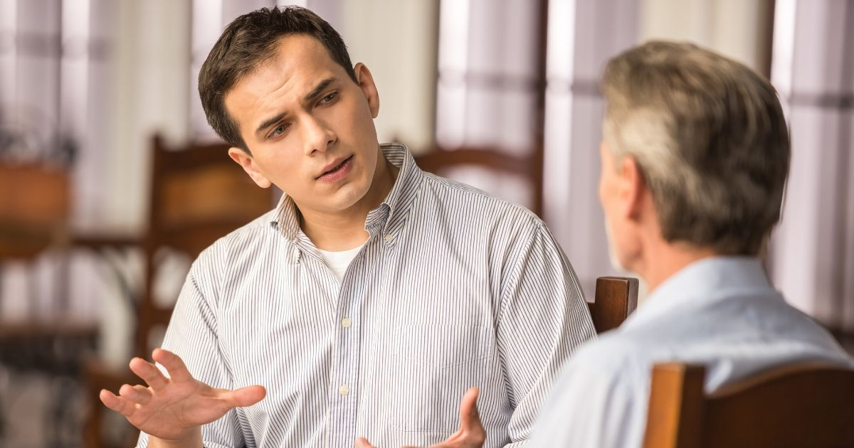 Two men engage in a discussion at a cafe table.