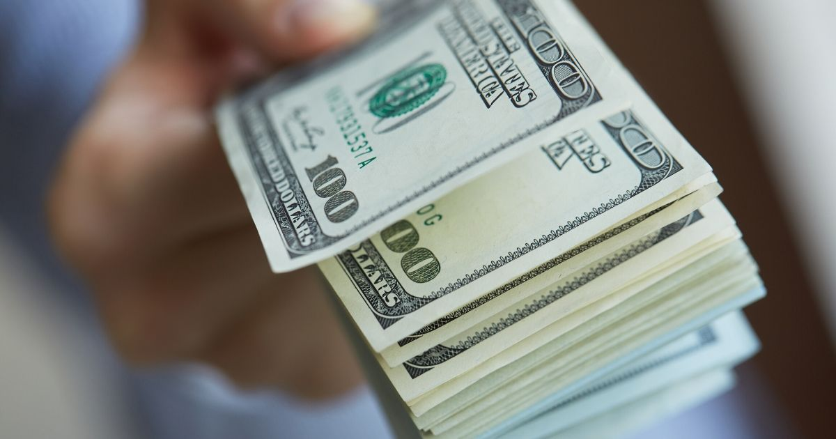 Pictured above is a stock image of a wad of bills in a person's hand.
