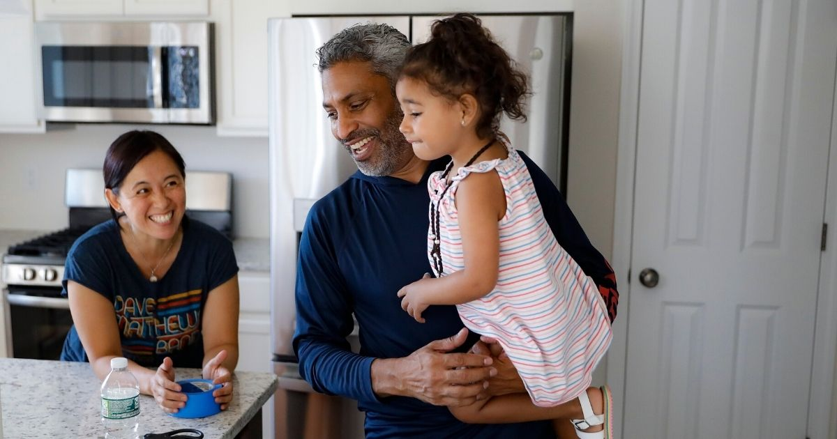 Anil Lilly holds his granddaughter alongside his wife, Joyce, at their new home in Washingtonville, New York, north of New York City.
