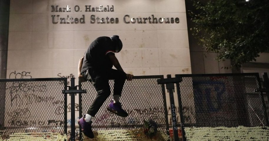A protester climbs the fence in front of the Mark O. Hatfield federal courthouse in downtown Portland, Oregon, as the city experiences another night of unrest on July 26, 2020.
