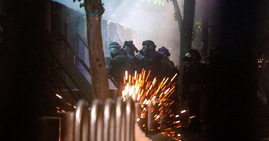 Federal law enforcement officers face off with violent demonstrators against the fence outside the Mark O. Hatfield Federal Courthouse sidewalk on July 29, 2020, in Portland, Oregon.