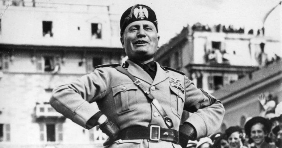 Italian dictator Benito Mussolini stands on a platform while addressing the workmen of a munitions factory in Genoa, Italy, on May 8, 1938.