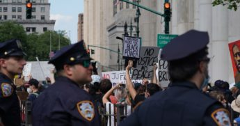 New York City police officers look on as protesters march into Manhattan from the Brooklyn Bridge on June 19, 2020, over the death of George Floyd in Minneapolis police custody on May 25.