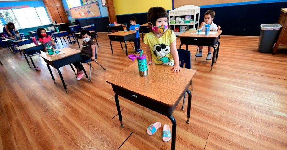 Children in pre-school wear masks at desks spaced apart per coronavirus guidelines in Monterey Park, California, on July 9, 2020. North Carolina Gov. Roy Cooper has ordered schools to open for fall instruction -- as long as they meet safety precautions.