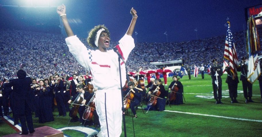 Whitney Houston sings the national anthem before Super Bowl XXV while tens of thousands of football fans wave tiny American flags in an incredible outburst of patriotism during the Persian Gulf War on Jan. 27, 1991, in Tampa, Florida.