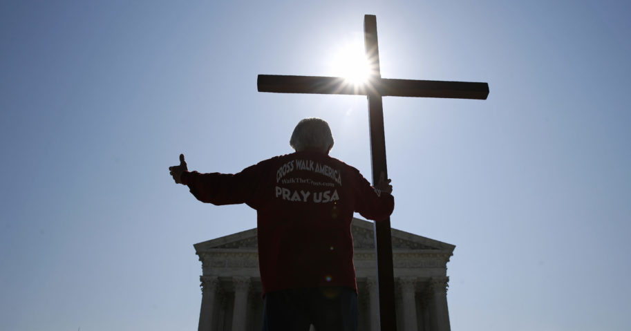 A man holds a cross outside the Supreme Court in Washington, D.C., on July 8, 2020.