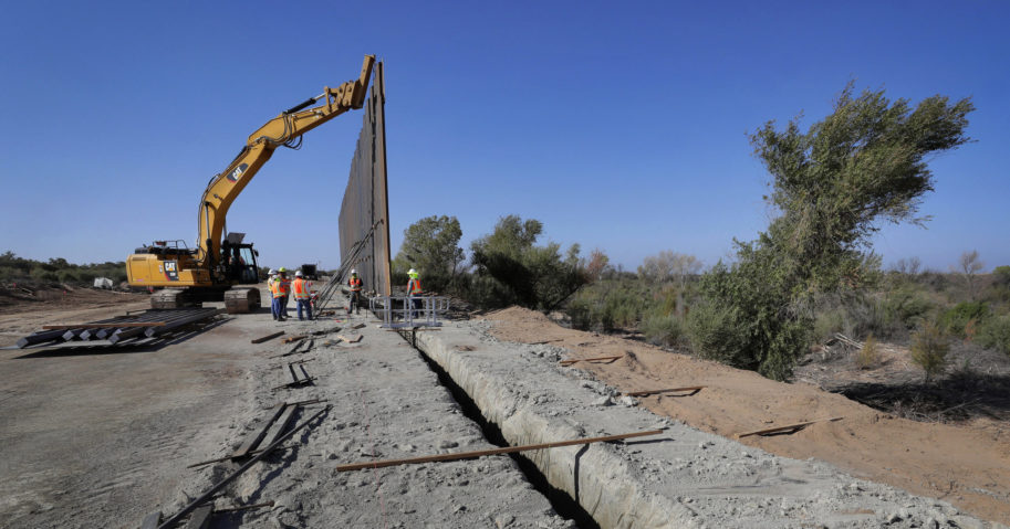 In this Sept. 10, 2019, file photo, government contractors erect a section of the border wall along the Colorado River in Yuma, Arizona. The federal Bureau of Land Management said on July 21, 2020, that it's transferred over 65 acres of public land in Arizona and New Mexico to the Army for construction of border wall infrastructure.