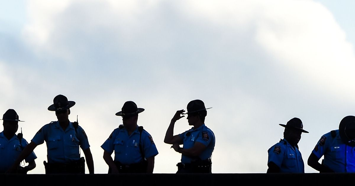 Police stand guard on a bridge as protesters block the road next to a burned Wendy's restaurant on the fourth day following Rayshard Brooks' death in the restaurant parking lot on June 16, 2020, in Atlanta, Georgia.
