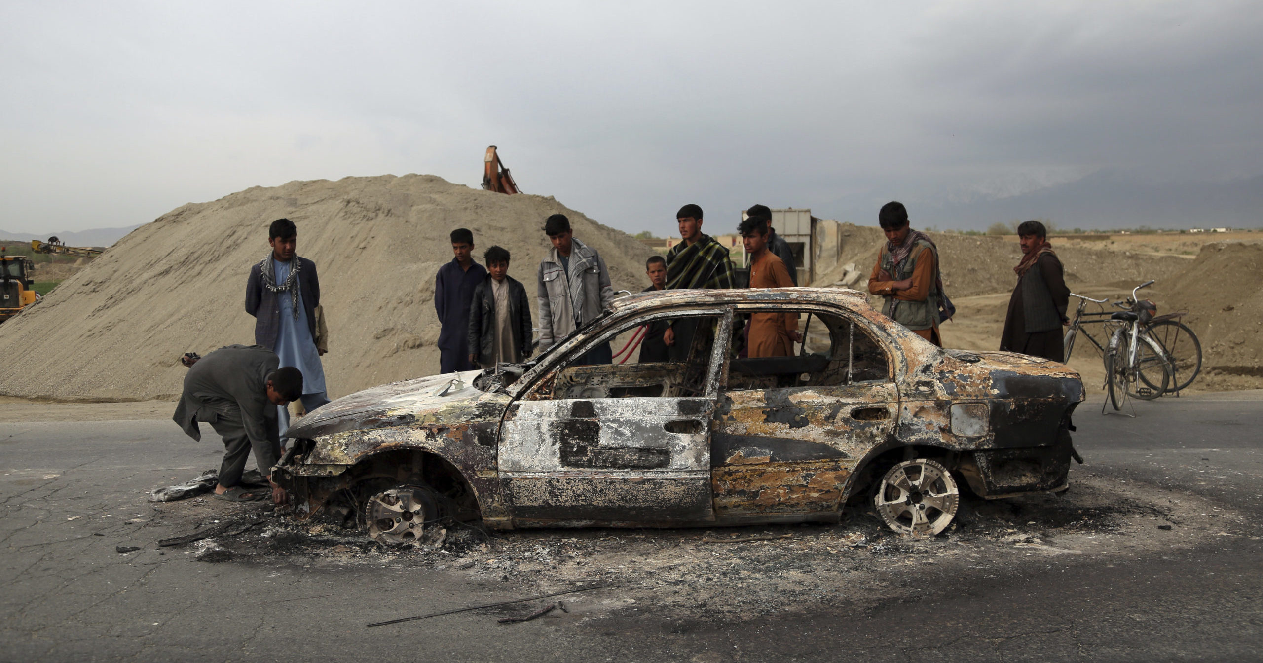 In this April 9, 2019, file photo, Afghans watch a vehicle burn after being shot by U.S. forces following a Taliban attack near the Bagram Air Base, north of Kabul, Afghanistan.