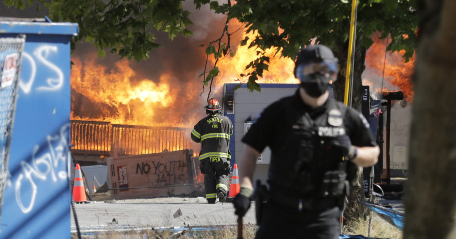 Construction buildings burn near the King County Juvenile Detention Center, Saturday in Seattle, shortly after a group of attackers left the area.
