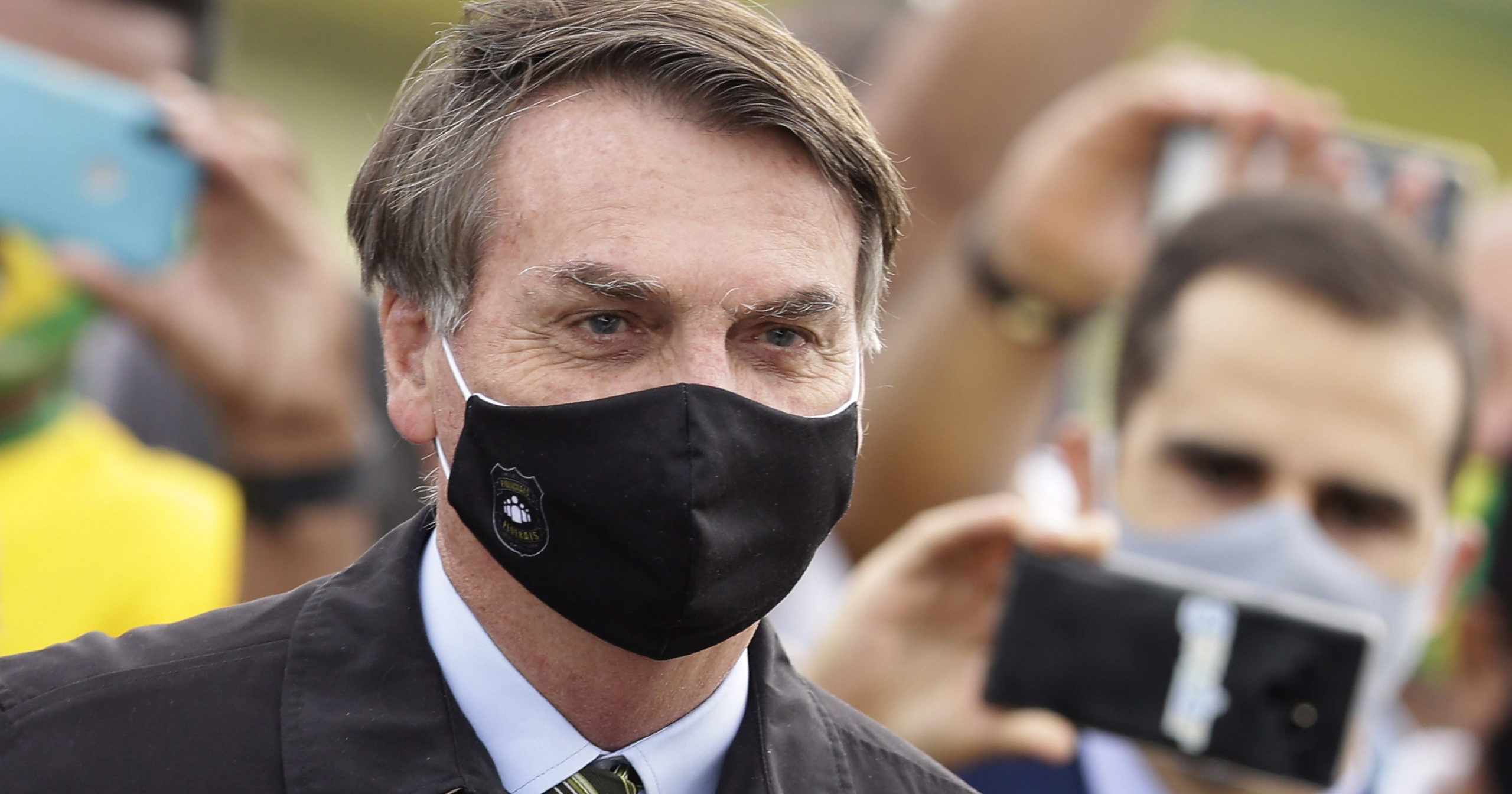 In this May 25, 2020, file photo, Brazilian President Jair Bolsonaro stands among supporters as he leaves his official residence in Brasilia, Brazil. Bolsonaro said on July 7 that he tested positive for COVID-19.