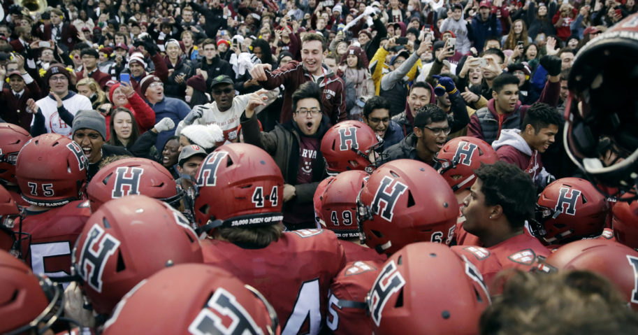 In this Nov. 17, 2018, file photo, Harvard players, students and fans celebrate their 45-27 win over Yale after an NCAA college football game at Fenway Park in Boston. The Ivy League has canceled all fall sports because of the coronavirus pandemic.