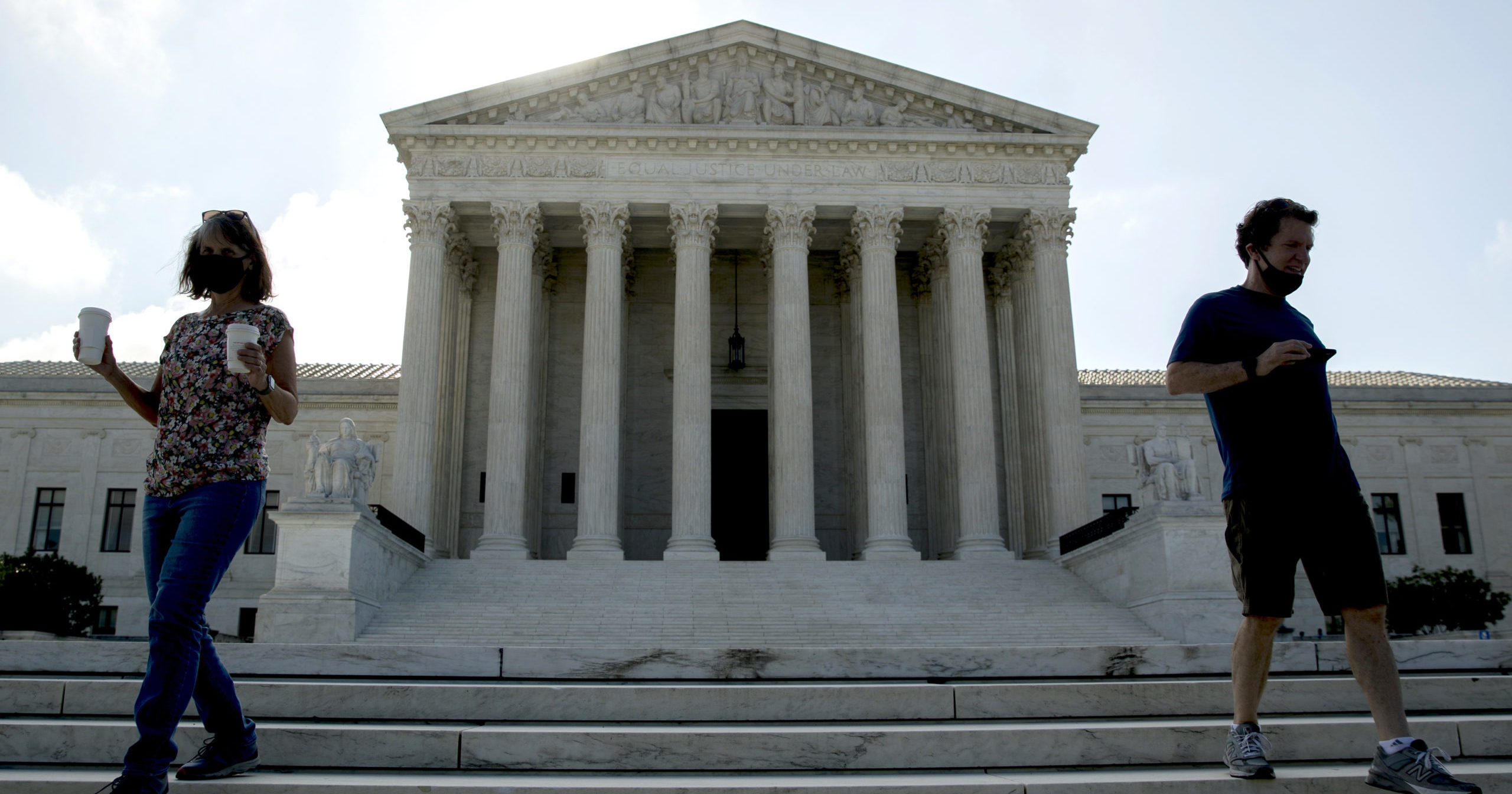Two people walk down the steps outside the Supreme Court on July 9, 2020, in Washington, D.C.