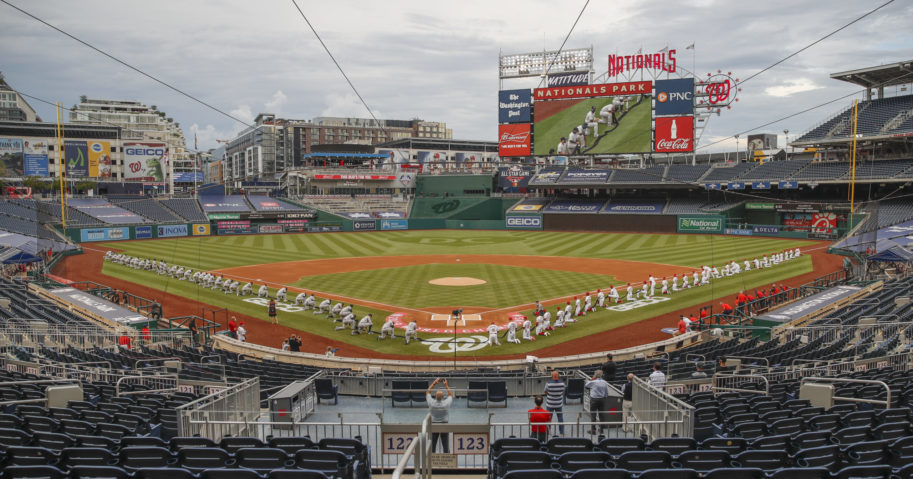 The New York Yankees and the Washington Nationals kneel while holding a black ribbon to honor Black Lives Matter before playing an opening day baseball game at Nationals Park on July 23, 2020, in Washington.