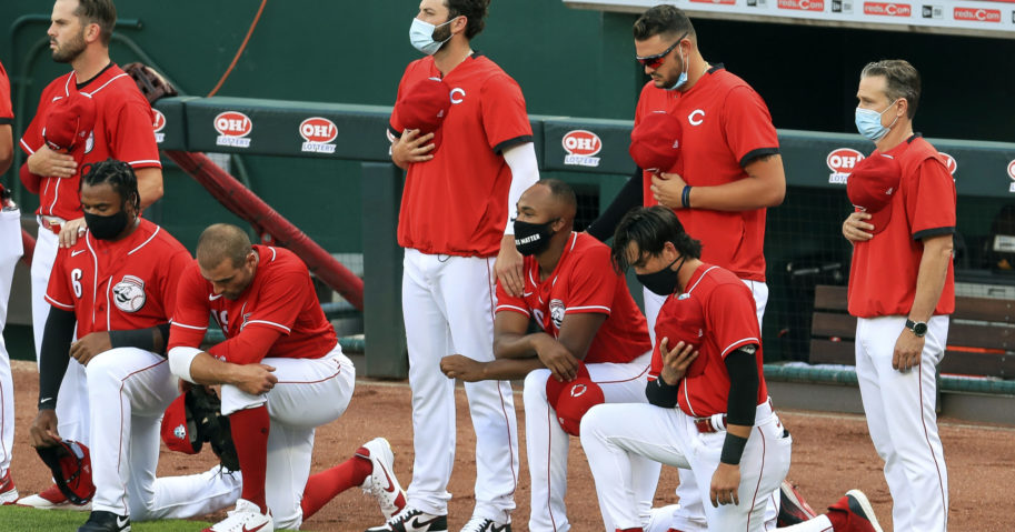 Cincinnati Reds' Phillip Ervin, left, Joey Votto, left middle, Amir Garrett, middle, and Alex Blandino, right, kneel during the national anthem prior to an exhibition baseball game against the Detroit Tigers at Great American Ballpark in Cincinnati on July 21, 2020.