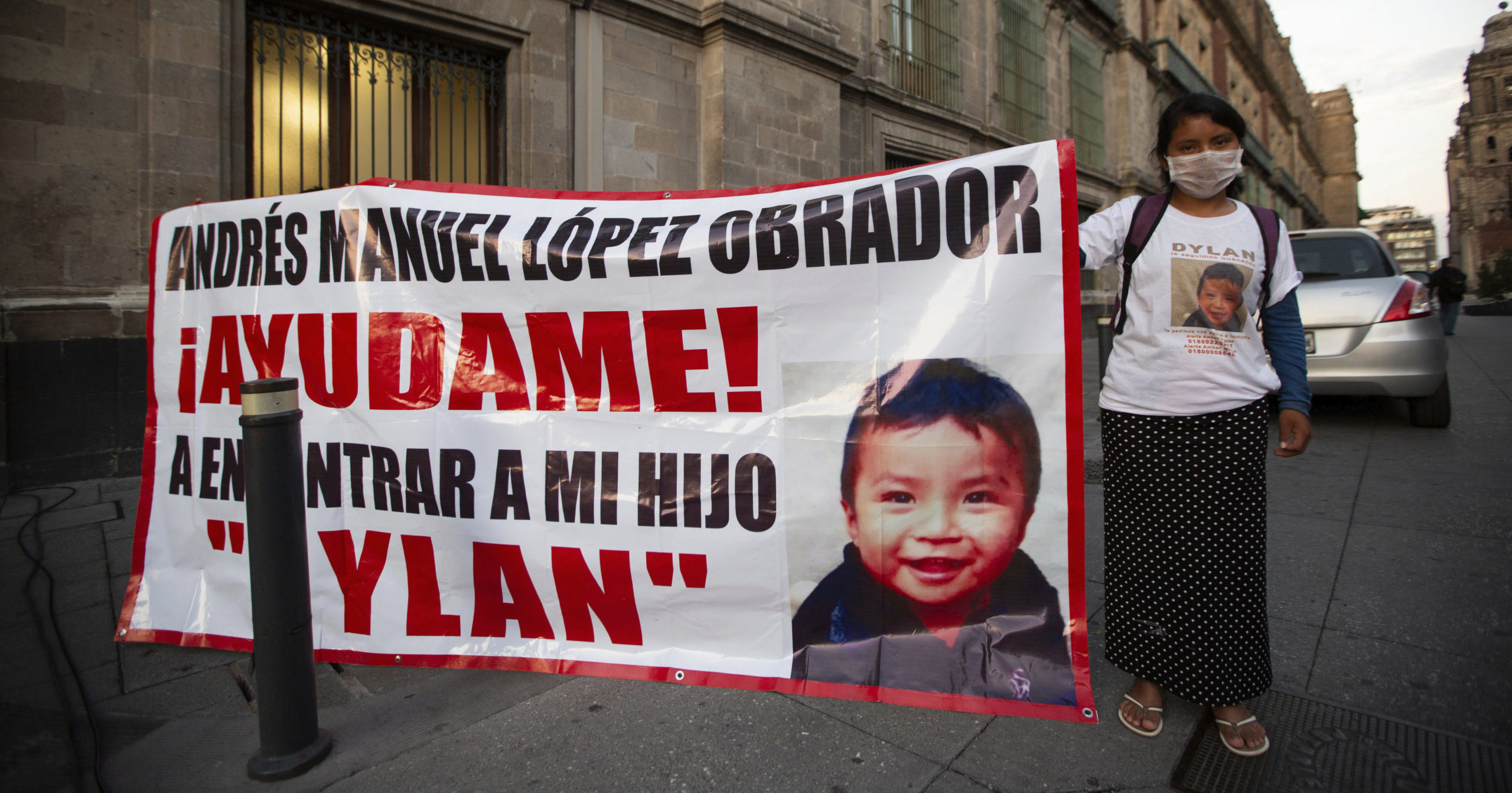 Juana Perez, whose 2-year-old son Dylan is missing, holds a poster of him outside the presidential palace in Mexico City on July 22, 2020. The search for the boy who was led away from a market in southern Mexico's Chiapas state three weeks ago led police to a horrifying discovery: 23 abducted children being kept in a house and forced to sell trinkets in the street.
