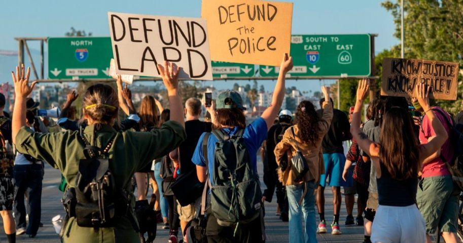 Protesters hold up signs as they block the freeway during a demonstration calling for the removal of District Attorney Jackie Lacey and to defund the police in Los Angeles on July 1, 2020.