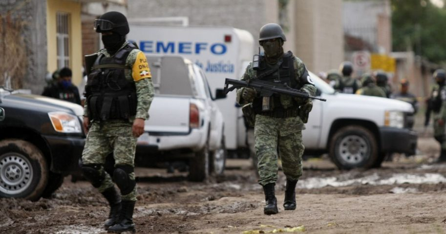 Members of the National Guard walk near the crime scene where 26 people were killed in Irapuato, Mexico, on July 1, 2020.