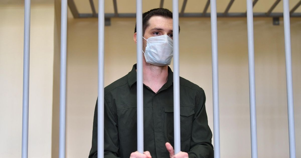 Former U.S. Marine Trevor Reed, charged with attacking police, stands inside a defendants' cage during his verdict hearing at Moscow's Golovinsky district court on July 30, 2020.