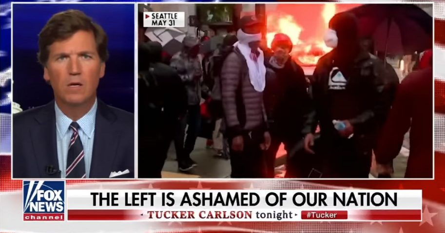Fox News host Tucker Carlson shares a screen with a still image from a fire burning at a riot.
