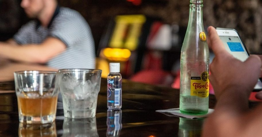 A bottle of hand sanitizer sits on a bar next to drinks at a restaurant in Austin, Texas, on June 26, 2020.