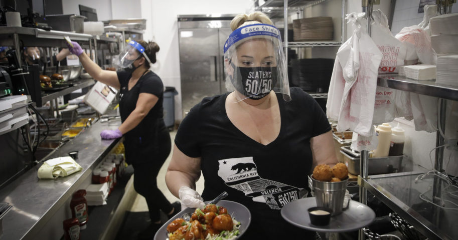In this July 1, 2020, file photo, a waitress takes a food order from the kitchen at Slater's 50/50 in Santa Clarita, California. Gov. Gavin Newsom announced a new process on Aug. 28, 2020, for reopening California businesses that is more gradual than the state's current rules.